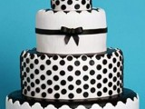a white wedding cake decorated with black polka dots, ribbons and patterns for a playful and fun look