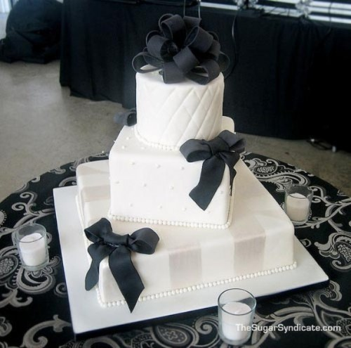 a white square wedding cake with various patterns on each tier, black ribbons and stripes