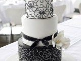 a black and white wedding cake with a solid tier and beautiful patterns plus a sugar bloom and a black ribbon bow