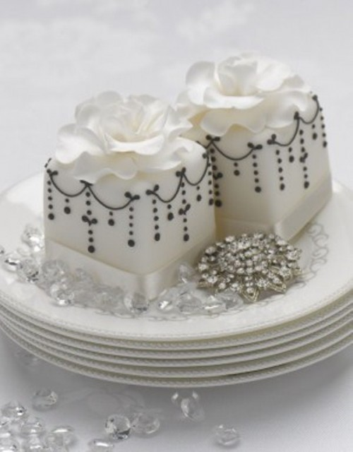 white square wedding mini cakes with black patterns and white sugar blooms on top