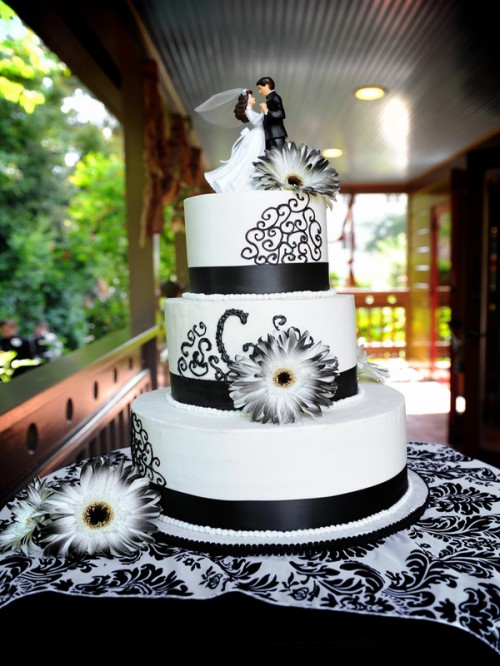 a black and white wedding cake decorated with ribbons, black patterns and sugar blooms plus a pretty topper