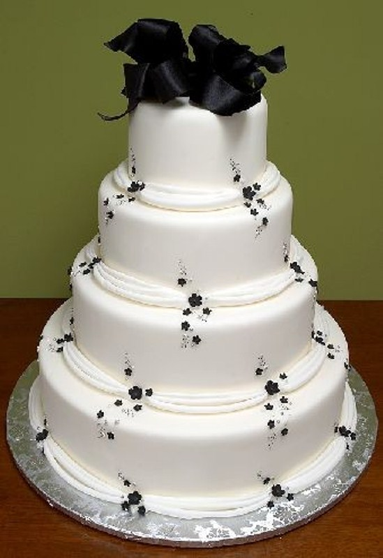 a white wedding cake decorated with small and subtle black flowers and a huge black ribbon bow on top