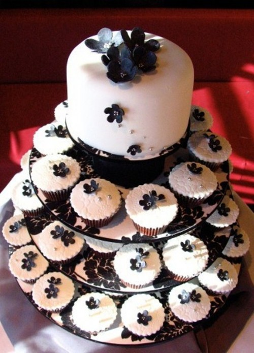 a modern white wedding cake decorated with black flowers and lots of matching cupcakes for a modern wedding