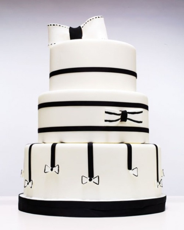 a white wedding cake decorated with black ribbons and bows, with a large sugar bow on top
