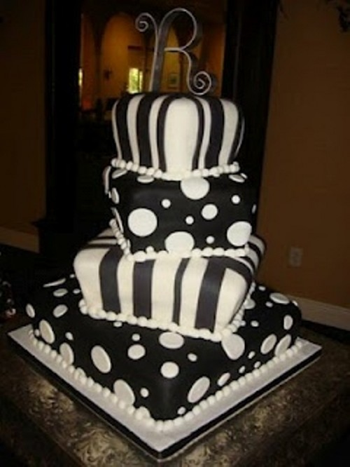 a bold square wedding cake imitating pillows in black and white, with polka dots and stripes