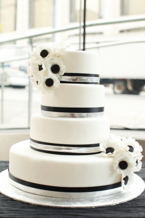 an elegant black and white wedding cake with stripes and matching anemones for a modern wedding