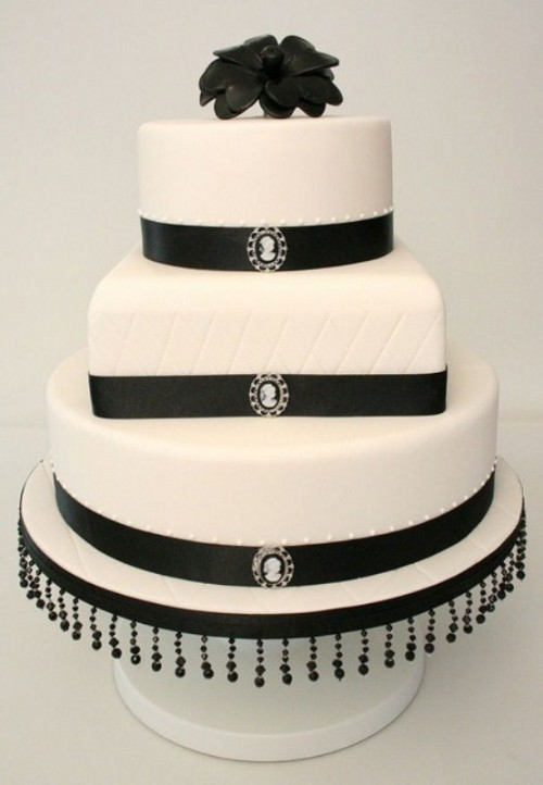 a timelessly elegant wedding cake in white decorated with black ribbons, brooches, beads and a sugar bloom on top
