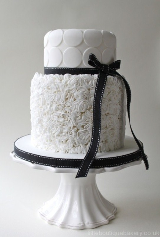 a white wedding cake with a textural and a polka dot tier plus black ribbons is a fresh take on classics