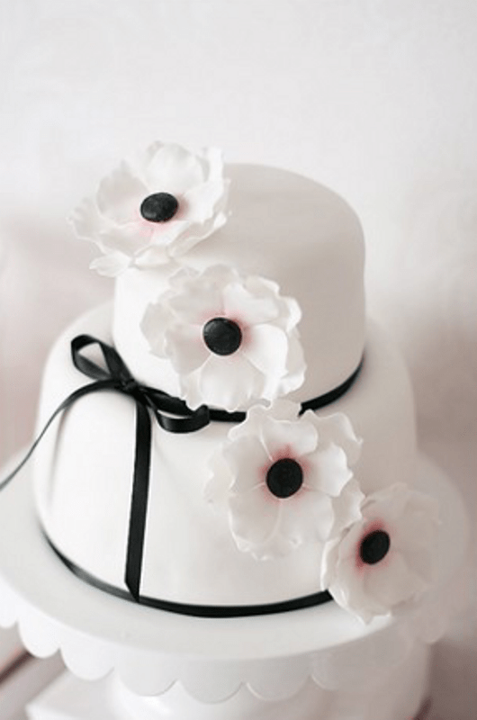 a white wedding cake spruced up with blakc ribbons and a bow plus some sugar anemones on top