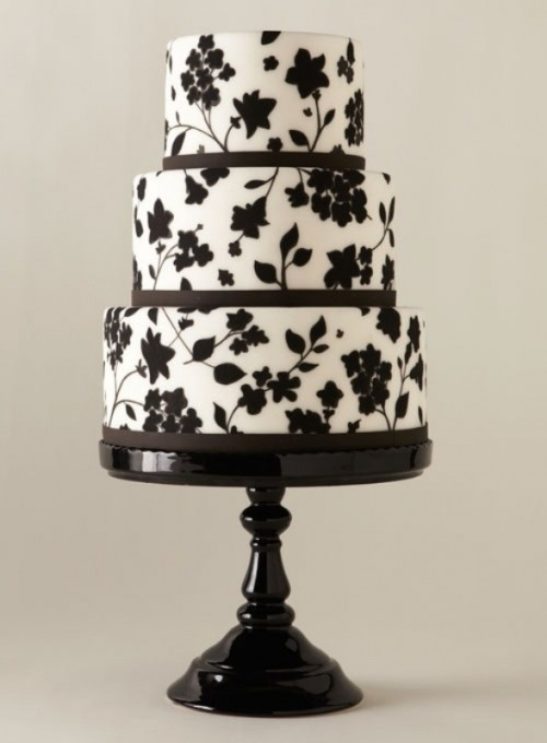 a white wedding cake decorated with black floral patterns and ribbons is a cool and bold idea to rock