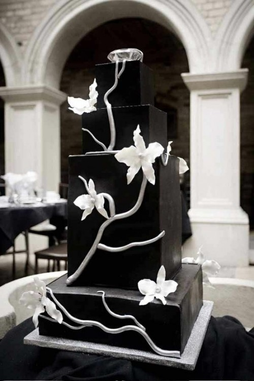 a black square wedding cake decorated with white sugar branches and flowers is a masterpiece