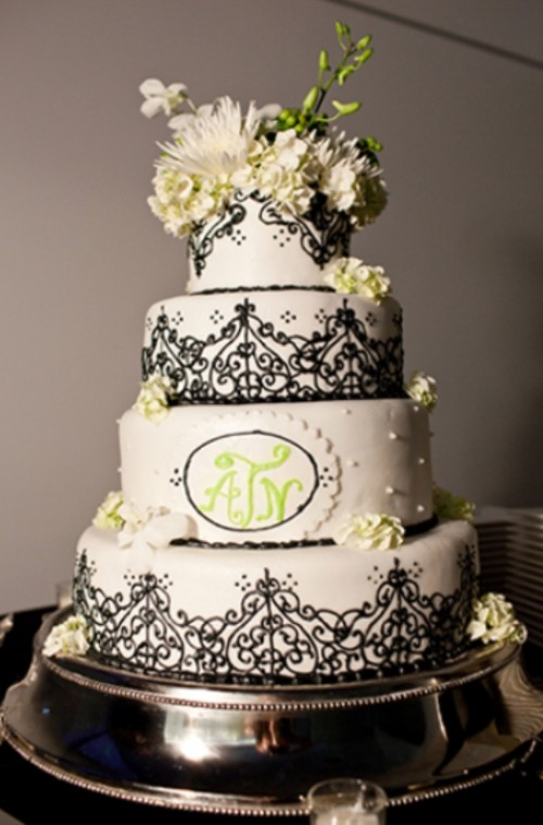 a black and white wedding cake decorated with lace and some sugar and fresh blooms and greenery