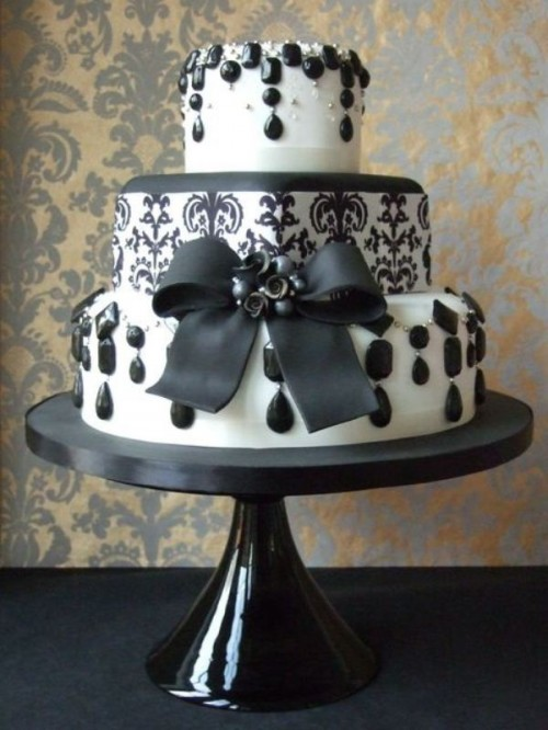 a black and white lace wedding cake decorated with edible rhinestones and a large ribbon bow