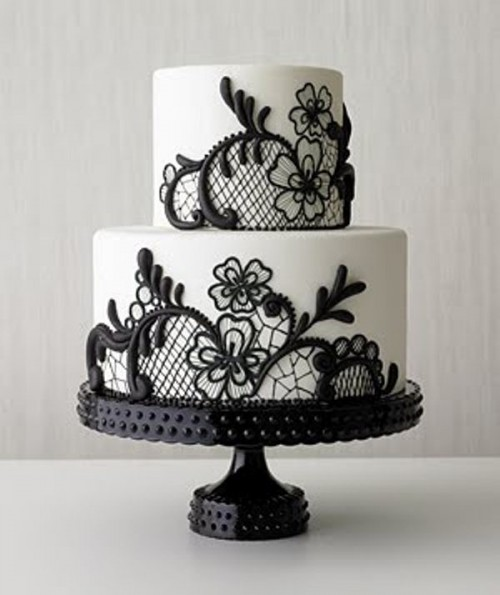 a white wedding cake decorated with blakc lace is a veyr refined idea