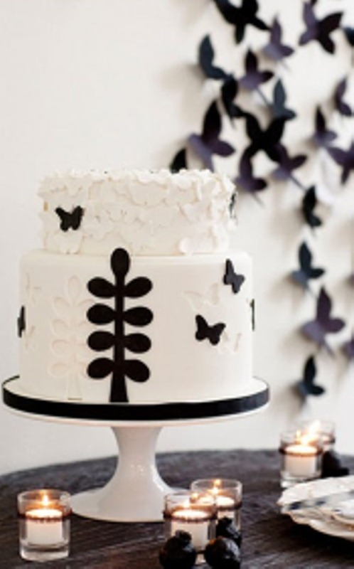 a black and white wedding cake with floral and butterfly appliques for a cute and whimsy wedding