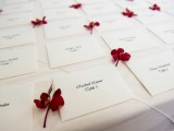 escort cards accented with deep red blooms are amazing for a fall or winter wedding