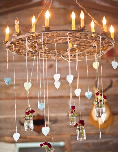 a wedding chandelier with candle-like bulbs, hearts hanging down and bottles with deep red blooms