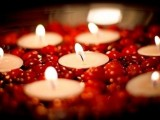 a wedding centerpiece of a bowl, some cranberries and floating candles to spruce up your fall or winter wedding decor