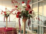 a tall wedding centerpiece of a gold tall vase and greenery, white and deep red blooms
