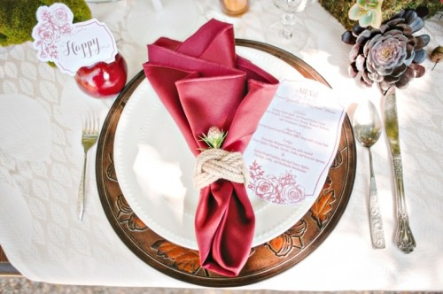 a metal charger, a white plate and a burgundy napkin accented with rope and a flower