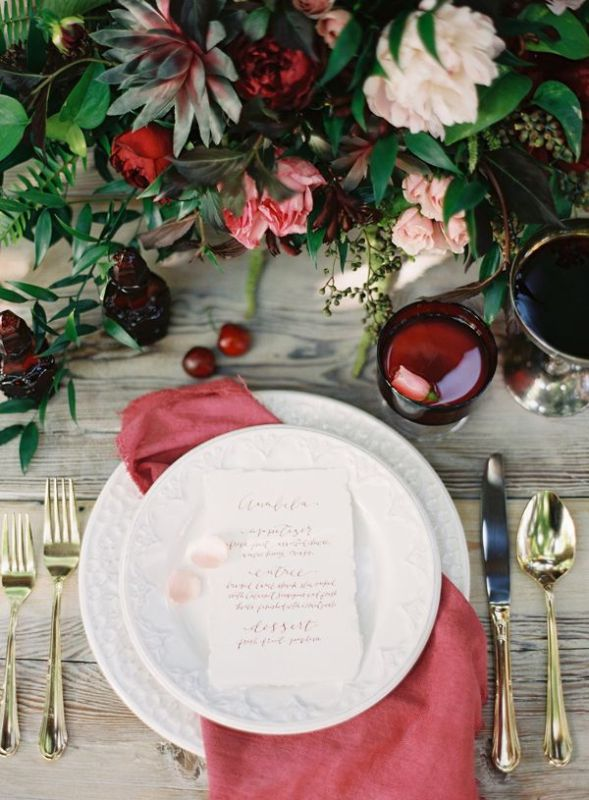 a deep red glass, a muted red napkin and a floral centerpiece with burgundy blooms accent the fall tablescape