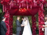 a deep red arch decorated with blooms and fabric will make your couple stand out a lot