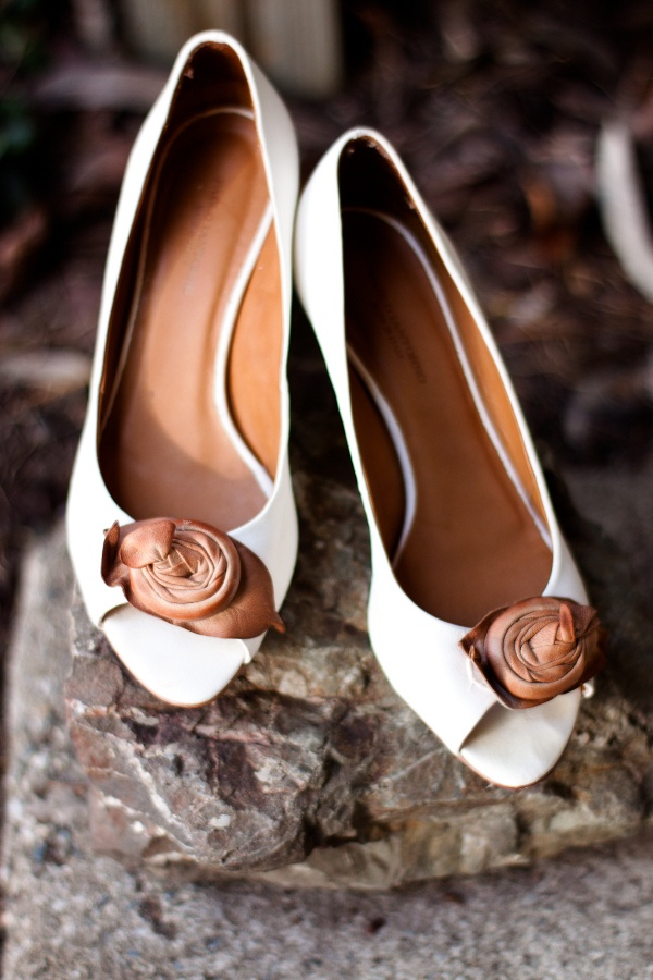 vintage white shoes with brown leather flowers look stylish and bold and add interest to the space