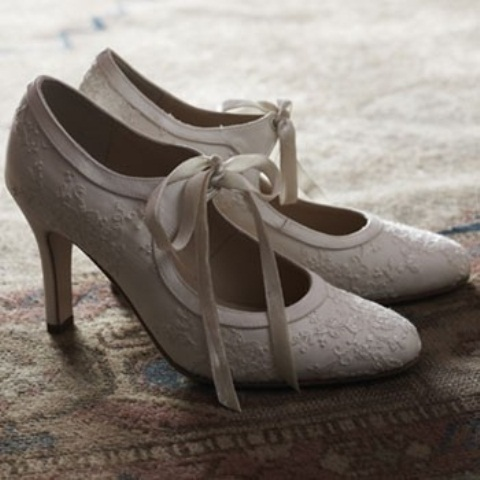 white vintage shoes of lace, with cutouts and ribbons bows look romantic and refined