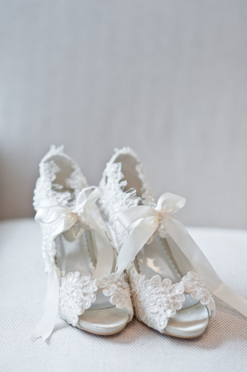 vintage white lace cutout wedding shoes with large ribbon bows look chic and refined
