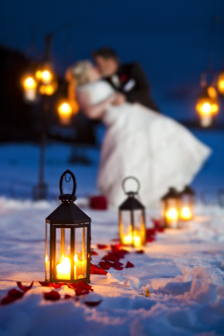 red petals and candle lanterns that line up a winter wedding aisle give it a cozy and chic feel