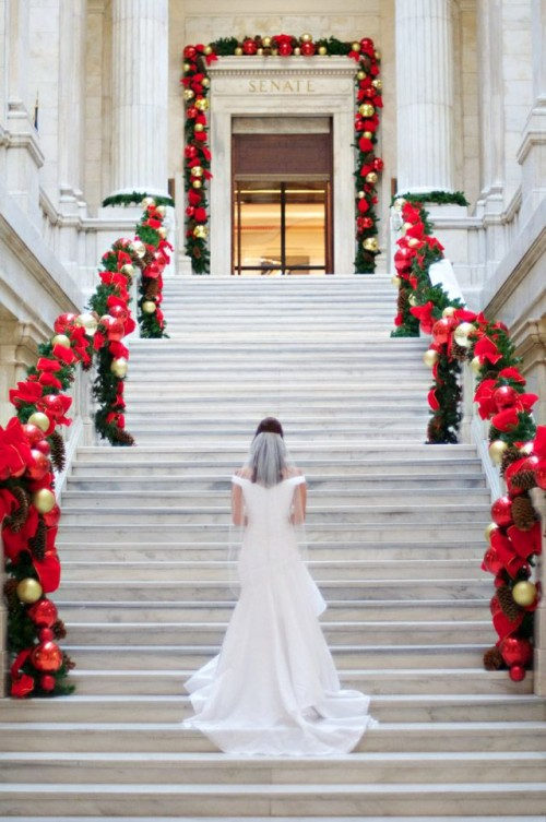 gorgeous bright garlands with evergreens, gold and red ornaments, red ribbon and bows make the railing cooler and brighter