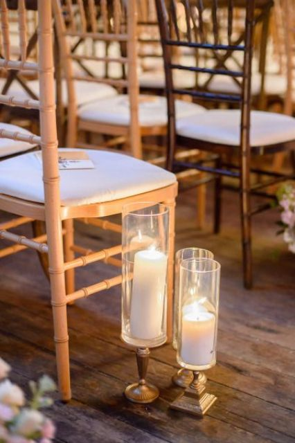 elegant pillar candles in candleholders and neutral blooms highlight the wedding aisle and make it elegant and chic