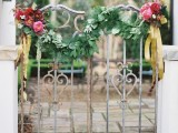 a gate decorated with greenery and blooms can be even used as a simple and cute wedding backdrop