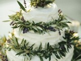 a white wedding cake decorated with lush greenery and lavender looks cool and won't cost you too much