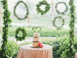 a greenery wedding arch with an assortment of greenery wreath doubles as a wedding dessert table backdrop