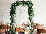 a lush greenery wedding arch will easily make your indoor ceremony feel more like an outdoor one