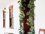 decorate wedding doorways with greenery and blooms to make your venue and ceremony space decor more romantic