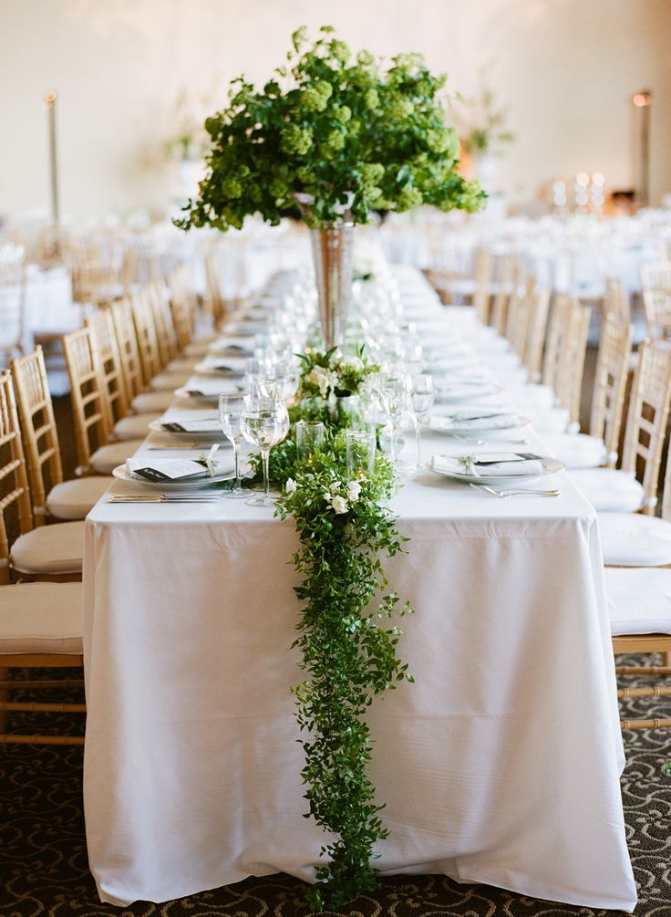 a lush greenery wedding centerpiece and a matching table runner make the tablescape look fresh and bold