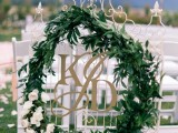 a large greenery wreath with white blooms will highlight your ceremony space or venue to make it frehs and bold