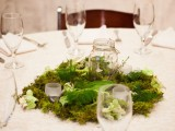 a lush moss and greenery centerpiece with a jar with candles is a great woodland and spring idea