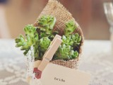 a cute wedding favor of a succulent wrapped in burlap, with a tag and a clothespin is a cute rustic idea