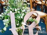 a greenery and white bloom decoration, with moss and pebbles plus LOVE letters is a creative wedding aisle decoration