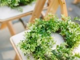 a lush greenery wreath to mark a chair is a cool idea to refresh your wedding ceremony space or venue