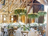 lush greenery chandeliers with candles will highlight the wedding venue a lot and will make it very fresh and spring-like