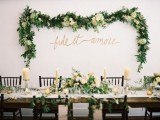 a lush greenery and white blooms garland on the wall match the centerpieces and make the venue look fresh and beautiful