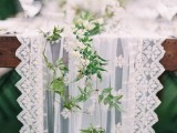 a white lace table runner paired with a greenery and white bloom one will make your table look fresh and ethereal
