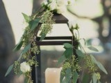 decorate a candle lantern with greenery and white blooms to make it feel outdoorsy and spring-like
