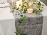 a grey burlap table runner with greenery and candles is a cool idea to refresh your wedding tablescape and make it more rustic