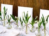 greenery and lily of the valley in clear glass bottles make the table look airy and ethereal