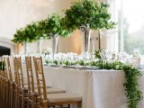 a lush greenery table runner and tall matching centerpieces make the tablescape look very fresh and very spring-like